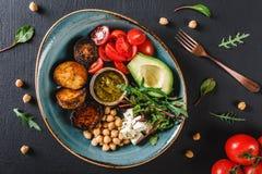 Plato sano del cuenco de Buda con el aguacate, el tomate, el queso, el garbanzo, la ensalada fresca del arugula, las patatas coci fotos de archivo