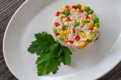 Plato vegetariano: un plato del arroz hervido, del maíz, de guisantes verdes y del swe fotos de archivo libres de regalías