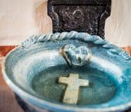 Plato vestíbulo-azul del agua santa con agua y la cruz-religión Fotografía de archivo