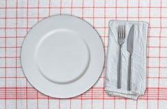 Plato y cubiertos vacíos en la toalla de cocina blanca roja Fotografía de archivo