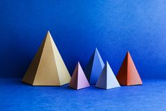 Platonic solid geometric figures. Three-dimensional pyramid rectangular objects on blue background. Yellow blue pink stock photography