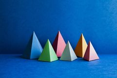 Platonic solid geometric figures. Three-dimensional pyramid rectangular objects on blue background. Yellow blue pink. Violet red colored tetrahedron abstract royalty free stock image