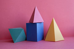 Platonic solids abstract geometric still life composition. Prism pyramid rectangular cube figures on pink paper Stock Images