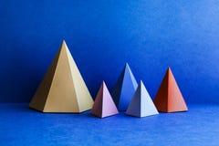 Platoniska fasta geometriska diagram Rektangulära objekt för tredimensionell pyramid på blå bakgrund Gula blåa rosa färger arkivbild