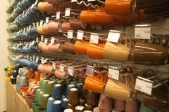 Platos brillantes, placas anaranjadas y blancas y tazas colocándose en el estante blanco Concepto de compra que elige los nuevos  foto de archivo