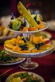 Platos con la fruta fresca cortada en una tabla festiva Fotografía de archivo libre de regalías