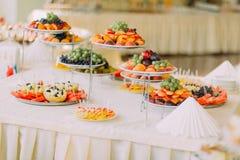 Platos con las frutas en la tabla de banquete del abastecimiento adornada por las servilletas blancas Imagenes de archivo