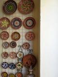 Platos de cerámica policromos que cuelgan en una cerca Fotografía de archivo libre de regalías