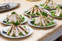 Platos de la carne en una tabla de banquete Fotografía de archivo
