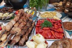 Platos de la carne y de pescados con las verduras en la tabla. Imagen de archivo