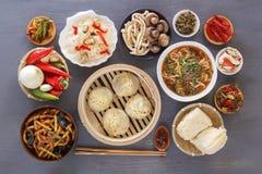 Platos de la cocina china en el surtido Cueza las bolas de masa hervida al vapor, tallarines, ensaladas, verduras, setas, marisco imagenes de archivo