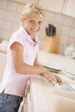 Platos de la limpieza de la chica joven foto de archivo