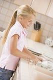Platos de la limpieza de la chica joven Foto de archivo libre de regalías
