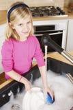 Platos de la limpieza de la chica joven que miran la cámara imágenes de archivo libres de regalías