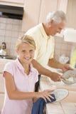 Platos de la limpieza del abuelo y de la nieta Imagen de archivo libre de regalías
