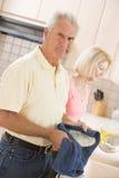 Platos de la limpieza del marido y de la esposa Imágenes de archivo libres de regalías