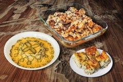 Platos de las piernas de pollo borrachas y de la ensalada rusa con la empanada del queso de la espinaca en viejo fondo de madera Fotos de archivo