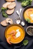 2 platos de sopa anaranjada de la calabaza en una tabla negra Tres camarones rojos adornan la sopa imagen de archivo