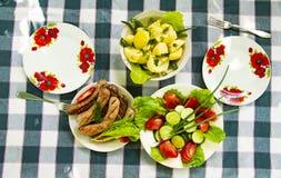 Platos en la tabla - verduras, patatas, salchichas bávaras imagen de archivo libre de regalías