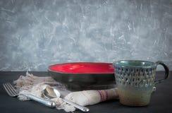 Platos hechos a mano de la arcilla de diversos colores en el hormigón negro platos, tazas tabla de cortar antigua imagen de archivo