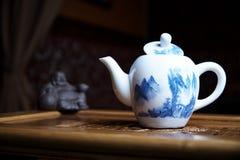 Platos hermosos para un primer de la ceremonia de té en un tablero de madera con las estatuas foto de archivo