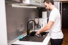 Platos permanentes y que se lavan del hombre joven feliz en la cocina imagenes de archivo