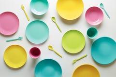 Platos plásticos coloridos en el fondo blanco Imagenes de archivo