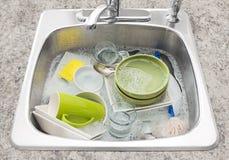 Platos que remojan en el fregadero de cocina Fotografía de archivo libre de regalías