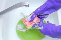 Platos que se lavan con la despedregadora de la esponja Manos en guantes de goma protectores fotos de archivo libres de regalías