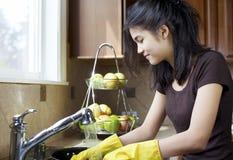 Platos que se lavan de la muchacha adolescente en cocina Imagen de archivo libre de regalías