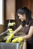 Platos que se lavan de la muchacha adolescente en el fregadero de cocina Imagen de archivo libre de regalías