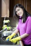 Platos que se lavan de la muchacha adolescente en el fregadero de cocina Imagenes de archivo