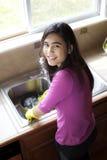 Platos que se lavan de la muchacha adolescente en el fregadero de cocina Fotografía de archivo libre de regalías