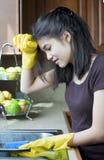 Platos que se lavan de la muchacha adolescente en el fregadero de cocina, cansado Fotos de archivo libres de regalías