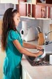 Platos que se lavan de la muchacha en la cocina Fotos de archivo libres de regalías