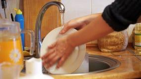 Platos que se lavan de la mujer en la cocina casera almacen de metraje de vídeo