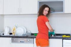 Platos que se lavan del ama de casa en los guantes de goma Imagenes de archivo