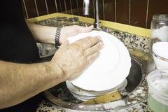 Platos que se lavan del hombre Imágenes de archivo libres de regalías
