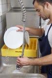 Platos que se lavan del hombre Imagen de archivo