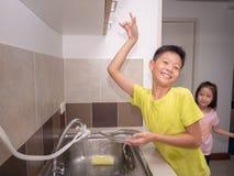 Platos que se lavan del muchacho adorable del niño en cocina nacional Havi del niño Foto de archivo libre de regalías