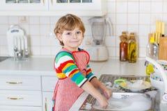 Platos que se lavan del pequeño muchacho rubio feliz del niño en cocina nacional Foto de archivo