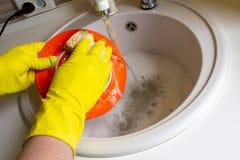 Platos que se lavan en guantes amarillos Foto de archivo libre de regalías