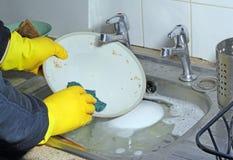 Platos sucios que se lavan en un fregadero. Fotografía de archivo