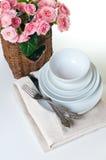 Platos, toallas y una cesta de flores Fotos de archivo libres de regalías
