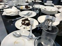 Platos, vidrios, cucharas y bifurcaciones blancos usados en la tabla en hotel imagenes de archivo