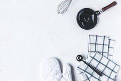 Platos y accesorios de la cocina para cocer en la tabla de cocina en un fondo blanco foto de archivo libre de regalías