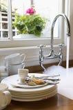 Platos y cubiertos sucios por el fregadero con la agua corriente Fotografía de archivo