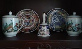 Plats antiques de céramique au-dessus des meubles en bois photographie stock libre de droits