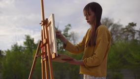 Plats av kreativitet Kvinnakonstnär som målar bilden på staffli lager videofilmer