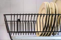Plats blancs séchant sur un support de plat en métal Support de séchage pour des plats photographie stock libre de droits